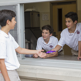 Middle School boys talking to each other through a window at The Regis School