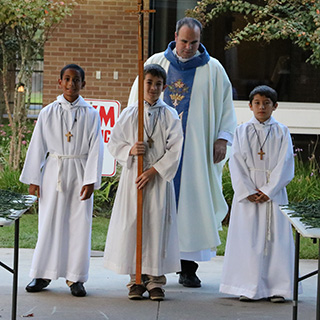 A Priest and a group of altar boys carrying a cross at The Regis School