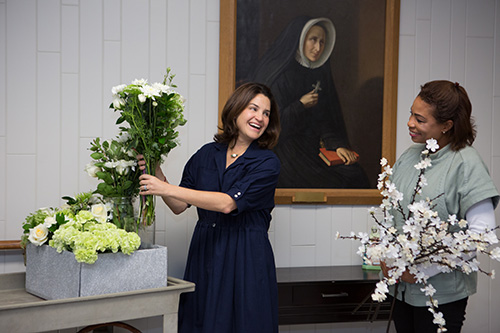 Two women holding flowers in front of an art piece